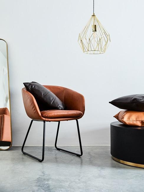 een leren fauteuil met een donkergrijs kussen naast de tafel
