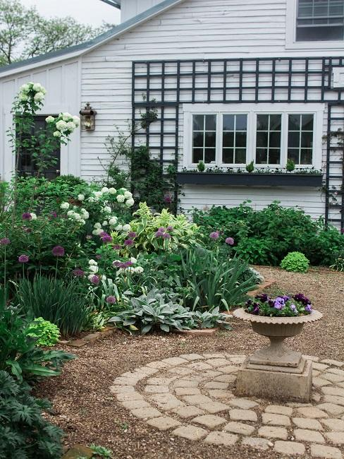Wit houten huis met grote achtertuin met veel peplanting en kiezels