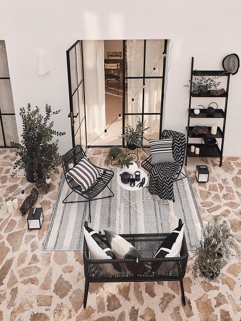 Top view van achtertuin met bruine stenen vloertegels met zwarte meubels