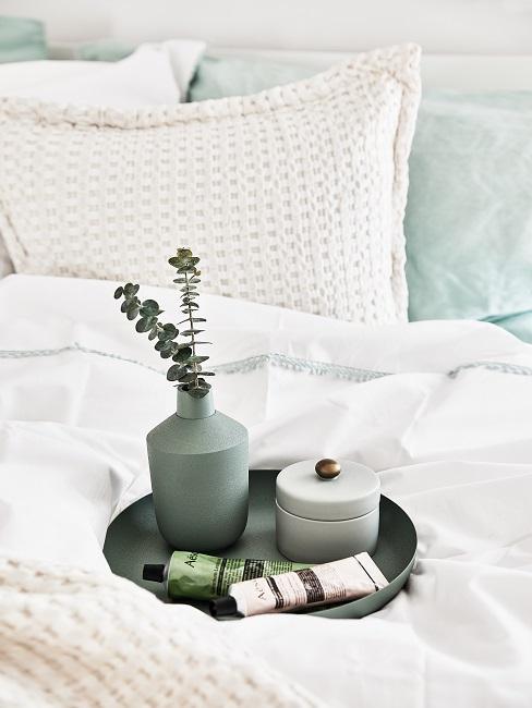 Bed met witte laken en kussen met grijsgroene accessoires