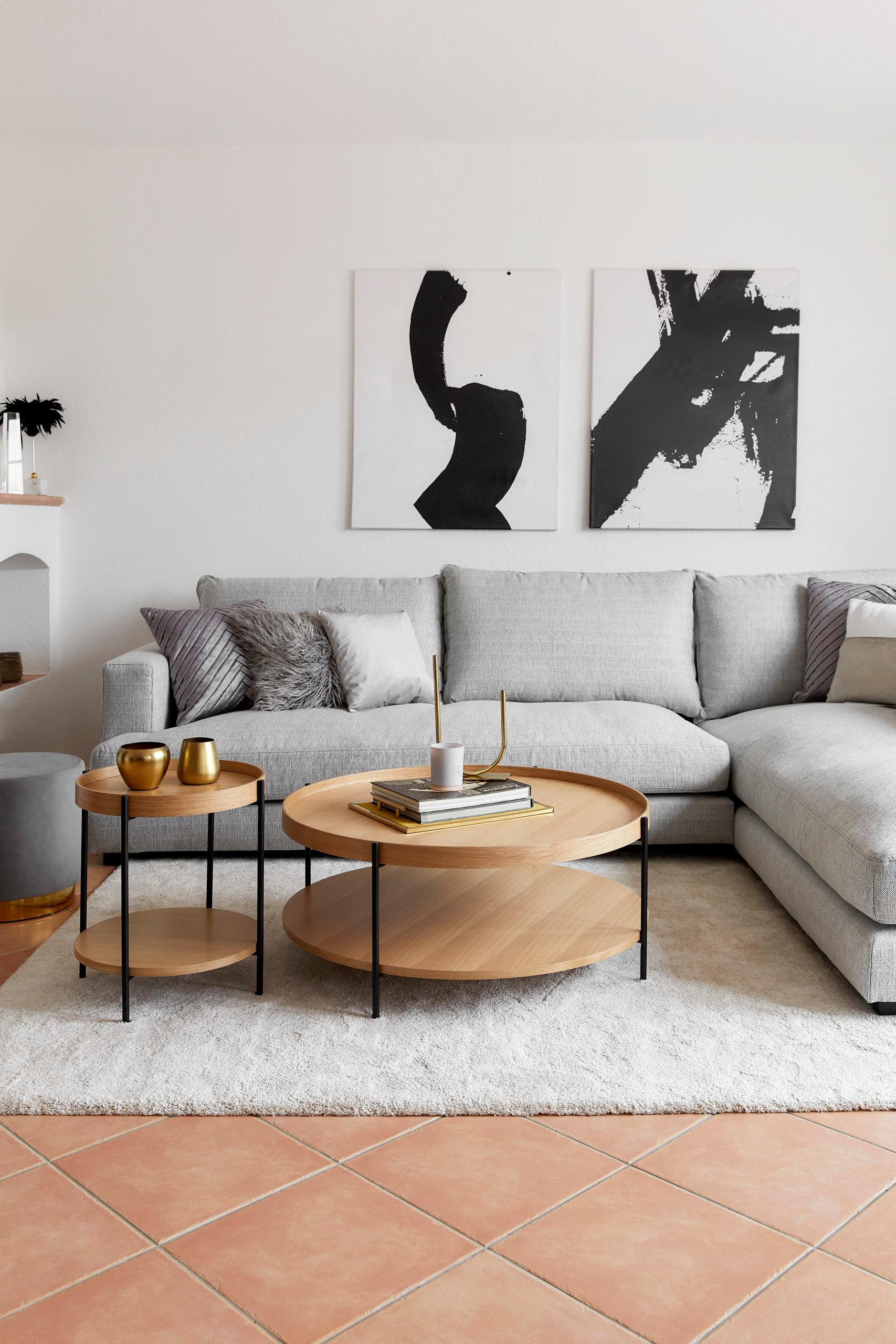 Witte woonkamer met grijze bank en houten salontafels op een grijs kleed