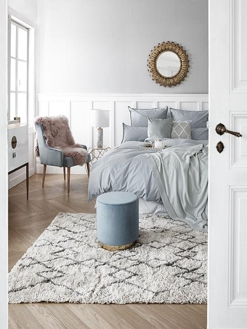 Grijze wand met witte lambrisering met blauwgrijs bed en poef