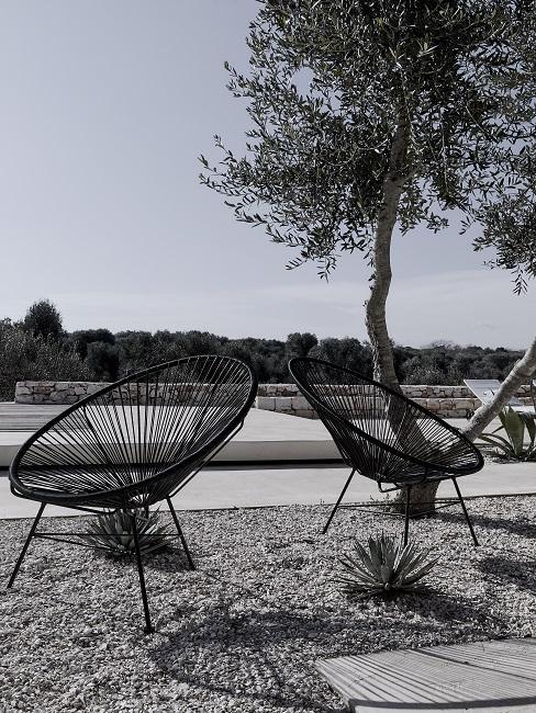 Zwarte lounge stoelen op grind met boom in een moderne tuin