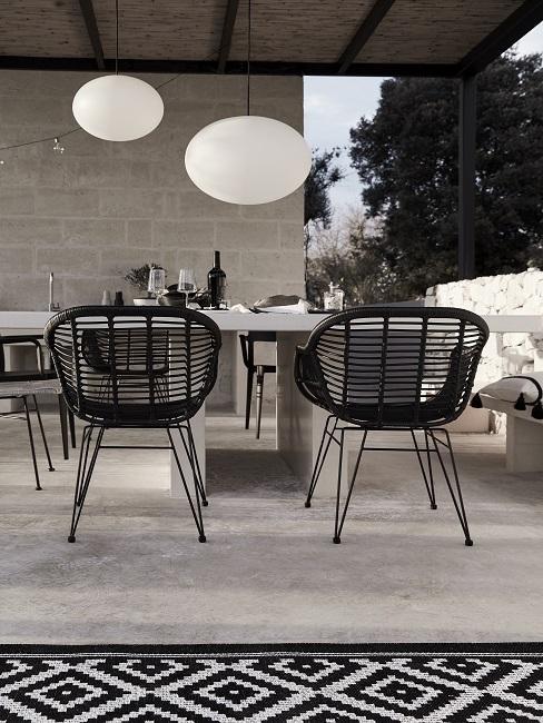Zwart wit tuin met grijze betonnen tafel en zwarte tuinstoelen