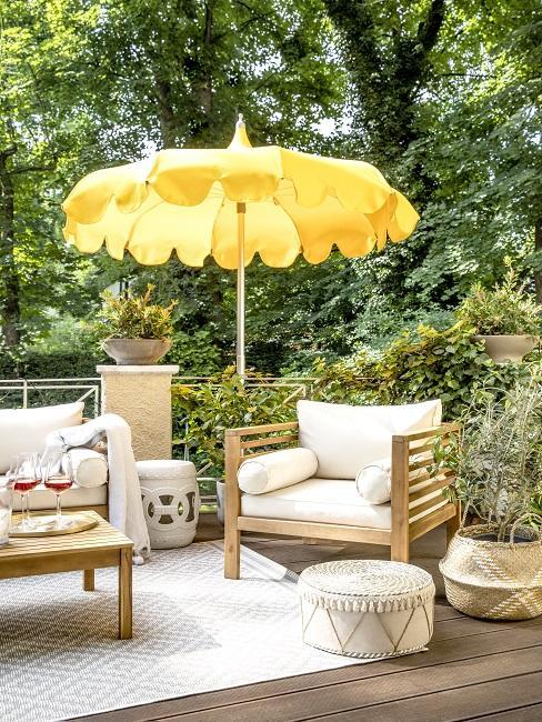 Balkon afschermen met beplanting en gele parasol met teakhouten tuinset