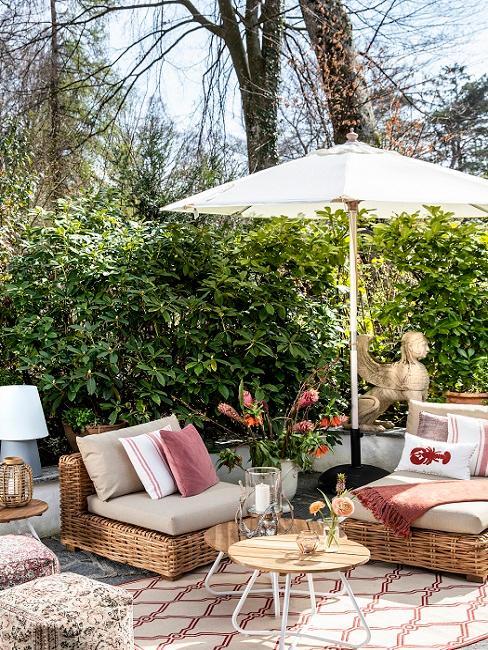 Tuin afschermen met groene planten en loungebank met kussens