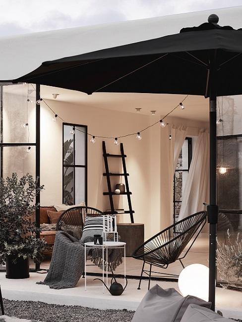 Zwarte tuinset met zwarte parasol naar binnen kijkend in huis