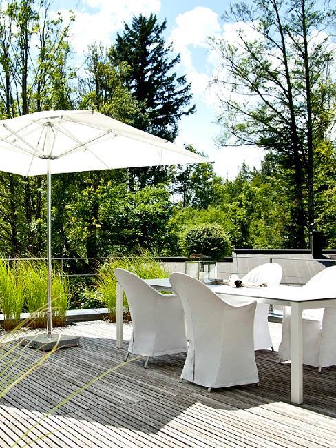 Witte outdoor meubelset met witte parasol op houten balkon vlonder