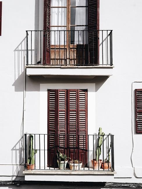 Frans balkon met wit huis met bruine luiken voor de houten ramen