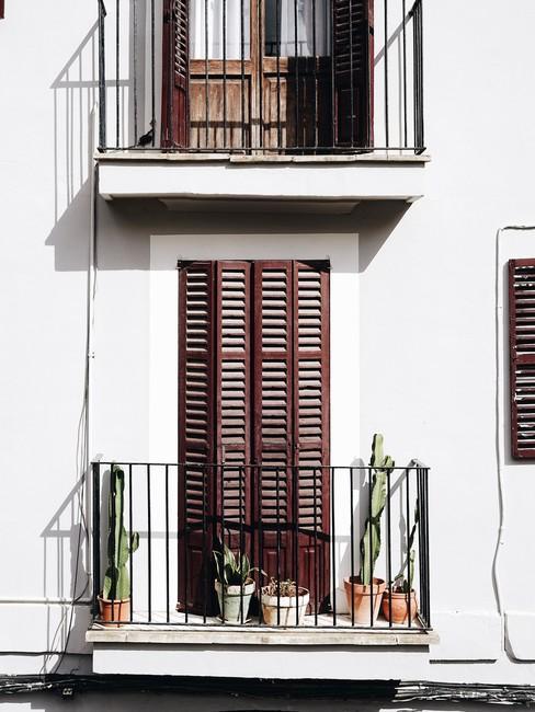 Wit huis met bruine luiken voor ramen met frans balkon