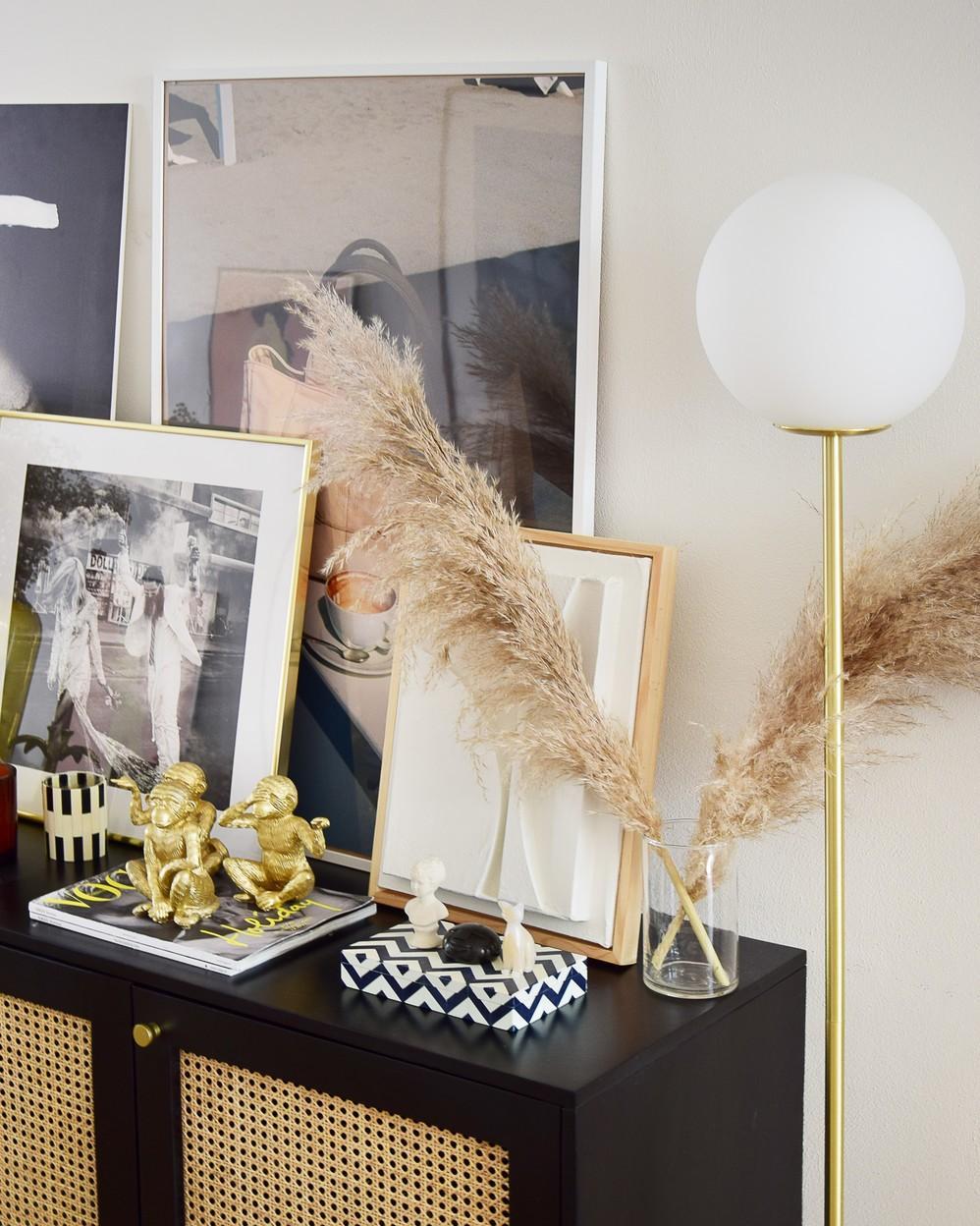 Retro design dressoirkast met weens vlechtwerk met bollamp en accessoires zoals schilderijen en foto's