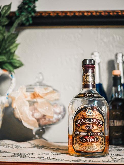 Fles whisky op houten sitetable met bloemen in vaas