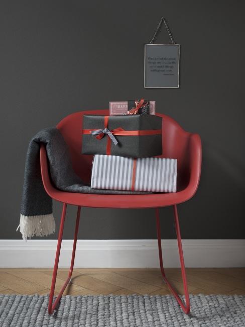 Rode leren stoel met cadeaus voor donkere muur