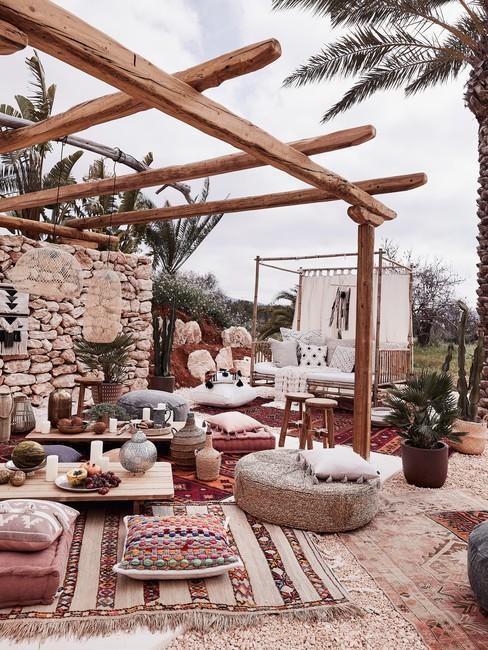 Houten pergola in bohemian style met vloerkleden en rotan gevlochten meubels
