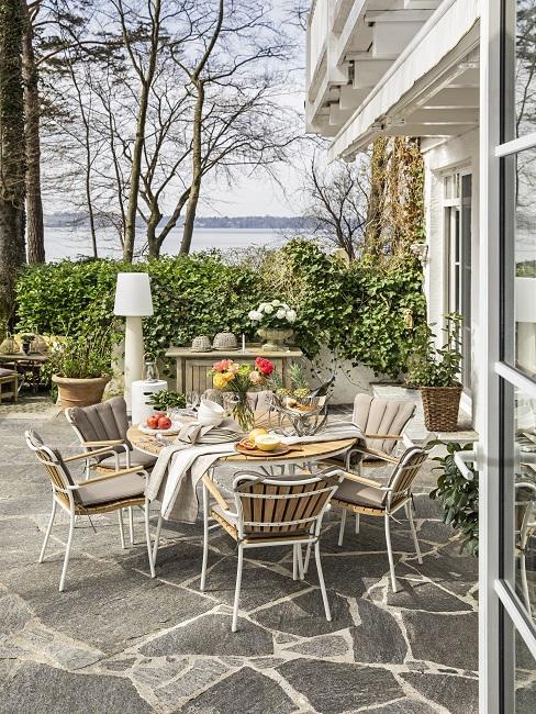 Tuin met houten meubelset met witte details met uitzicht op water