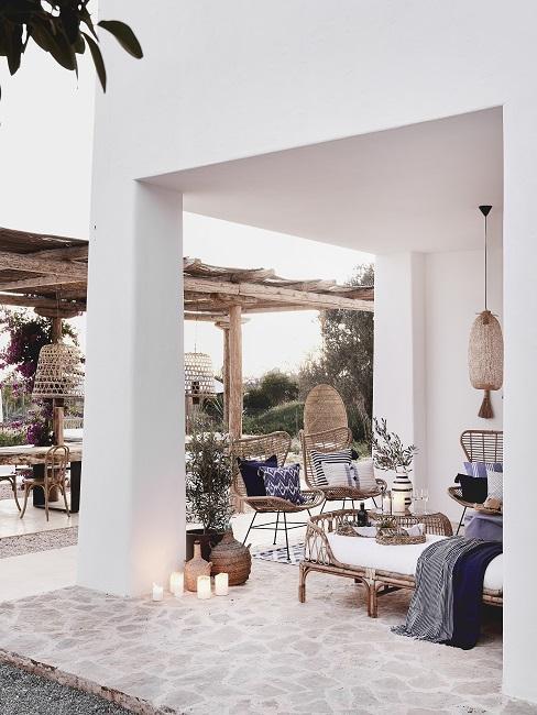 Ibiza stijl tuin met witte stenen pergola met bohemian meubels