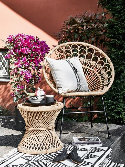Rotan meubels voor oud roze huis met bloemen