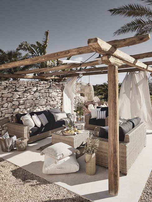 Houten pergola met witte lakens en rotan tuinset