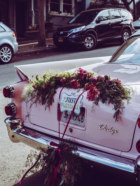 Roze auto met een close-up van de kofferbak met een bruiloft decoratie in boho stijl