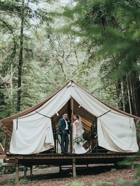 Bruidspaar voor de witte bruiloftstent in het woud