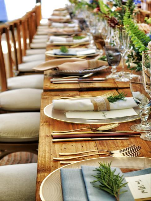 Gedekte tafel met goudkleurige bestekset en witte servetten en veel glazen