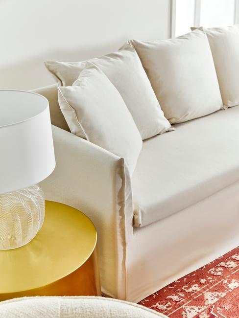 Witte bank voor rood vloerkleed met witte tafellamp op goude bijzettafel