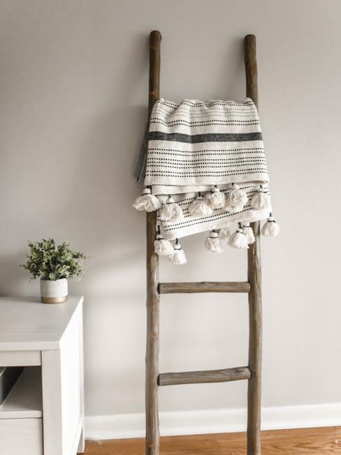 Decoratieve ladder met een plaid naast een witte tafel met een potplant