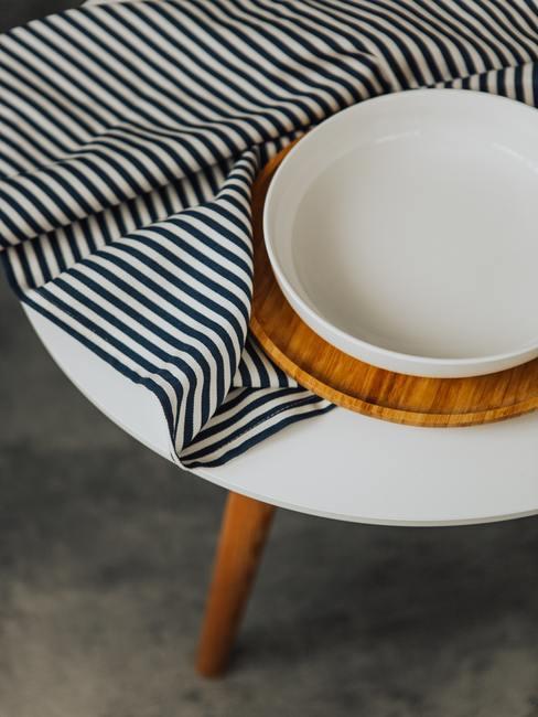 Witte tafel met gestreept tafelkleed decoratie en decoratieve mand in minimalistisch interieur
