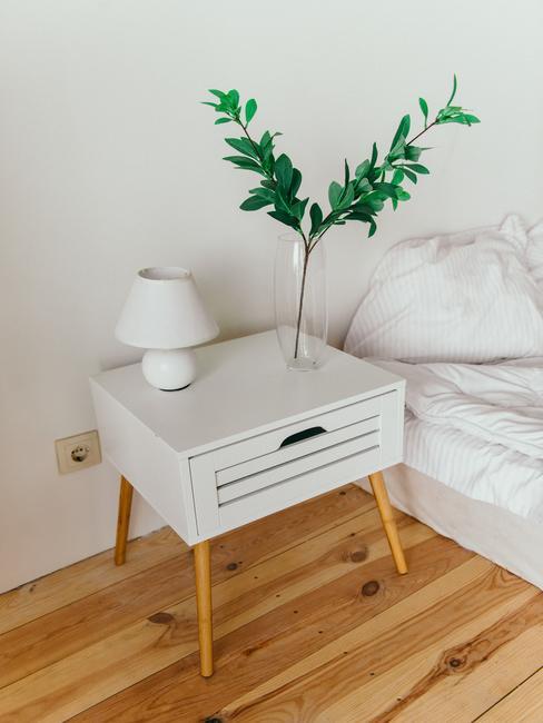 Witte slaapkamer met een onopgemaakt bed en nachtkastje met een transparante glazen vaas en een wit bedlampje