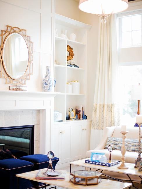 Woonkamer in wit met een decoratieve vergulde spiegel en witte meubels