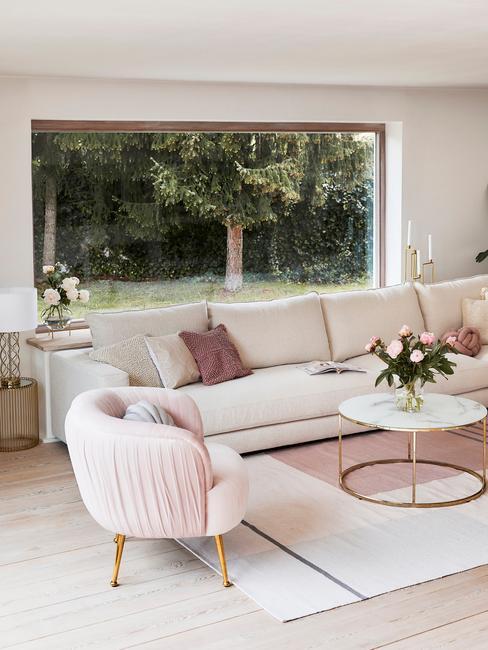 Romantisch interieur met roze stoel en creme bankstel