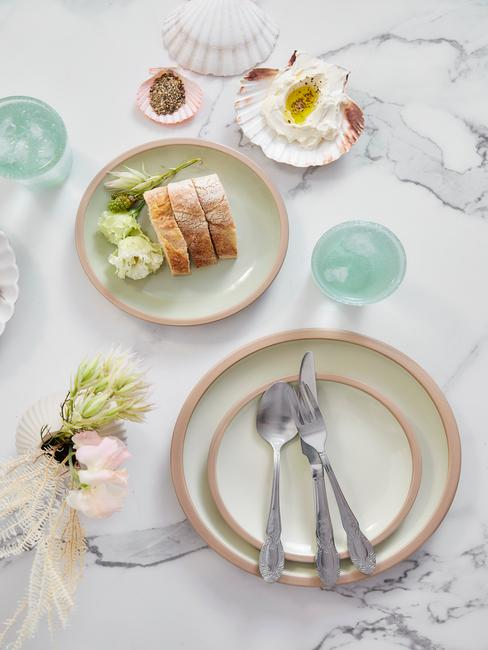 Zestaw talerzy położony na marmurowym stole