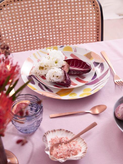 Kolorowe talerze położone na różowym obrusie wraz ze złotymi sztućcami