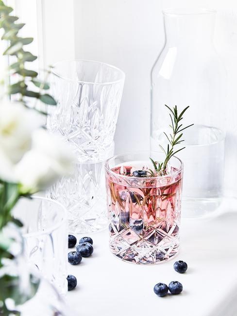 Drink Blackberry Gin Fizz w krysztełowej szklance postawiony na białym stole z karafką