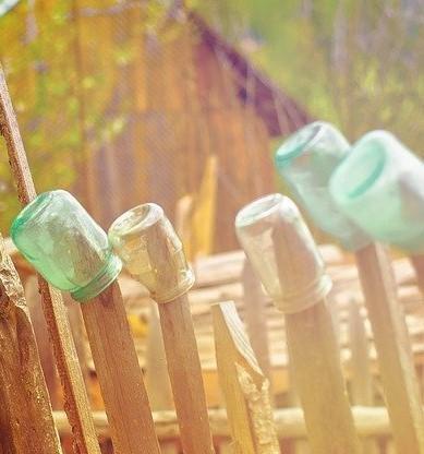 Drewniany płot na którym znajdują się szklane słoiki