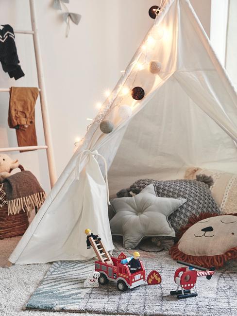 Biały namiot w pokoju dziecięcym z poduszkami w środku, oświetleniem oraz zabawkami