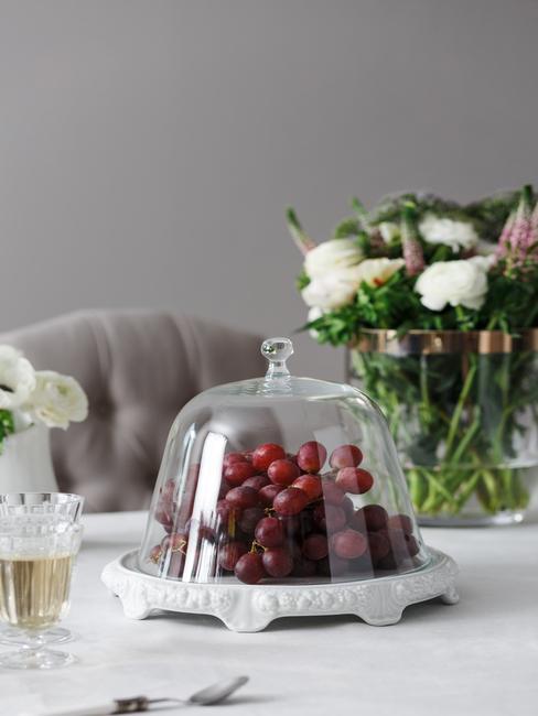 Nakryty stół białym obrusem, na którym znajdują się kwiaty oraz dekoracyjna patera z owocami