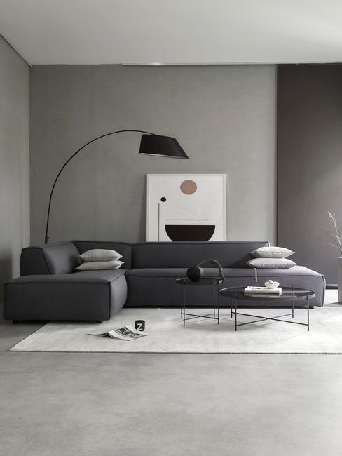Cały szary salon z dużą kanapą, lampą oraz obrazem