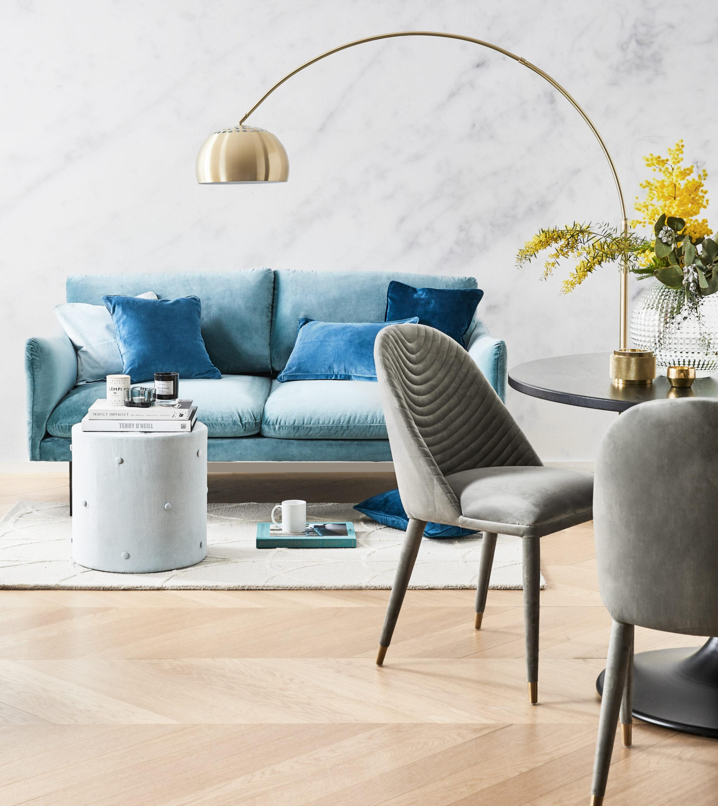 Szary salon z szarymi krzesłąmi, pufem, złotą lampą i niebieską kanapą