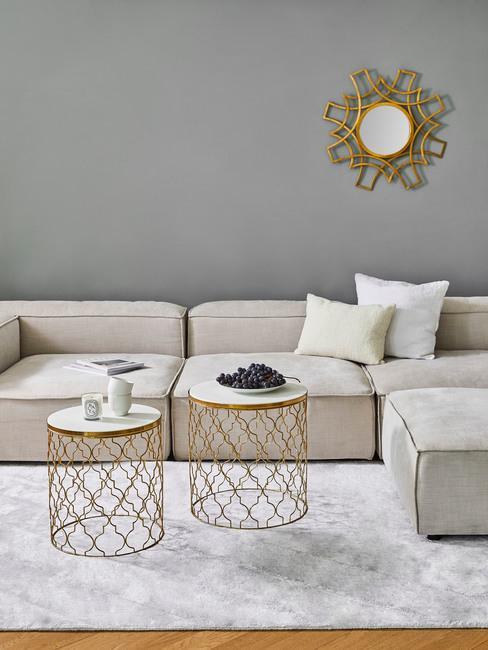 Szary salon, beżową kanapą oraz złotym lustrem