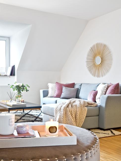 Salon na poddaszu z jasnobłękitną kanapą, stolikiem na kawę oraz dekoracjmi i dywanem