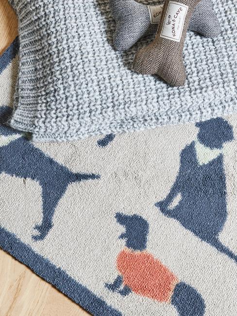 Błękitny koc na psa leżący na macie ze wzorami z psami
