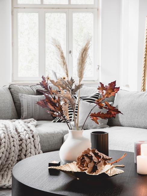 Biały wazon na tle szarej kanapy z suszonymi kwiatami