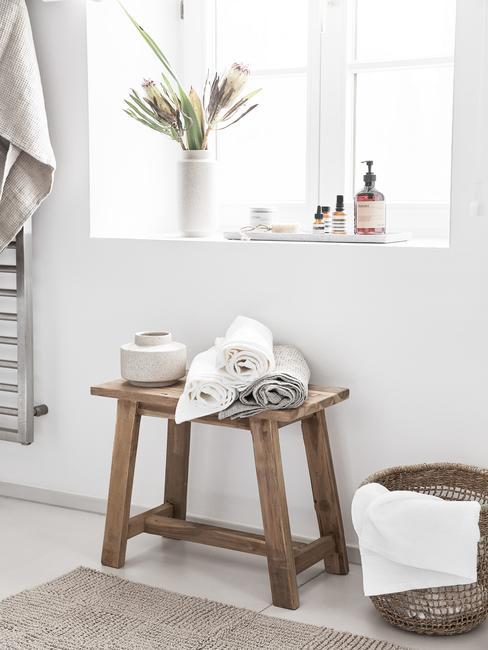 Drewiany stołek na którym leżą zwinięte , jasne ręczniki. W tle oko i szeroki parapet