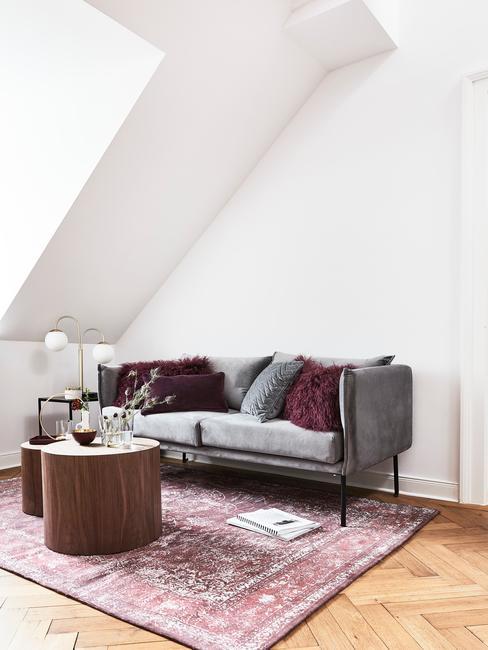 Mały salon na poddaszu z szarą sofą, vintage dywanem i drewnianymi stolikami pomocniczymi
