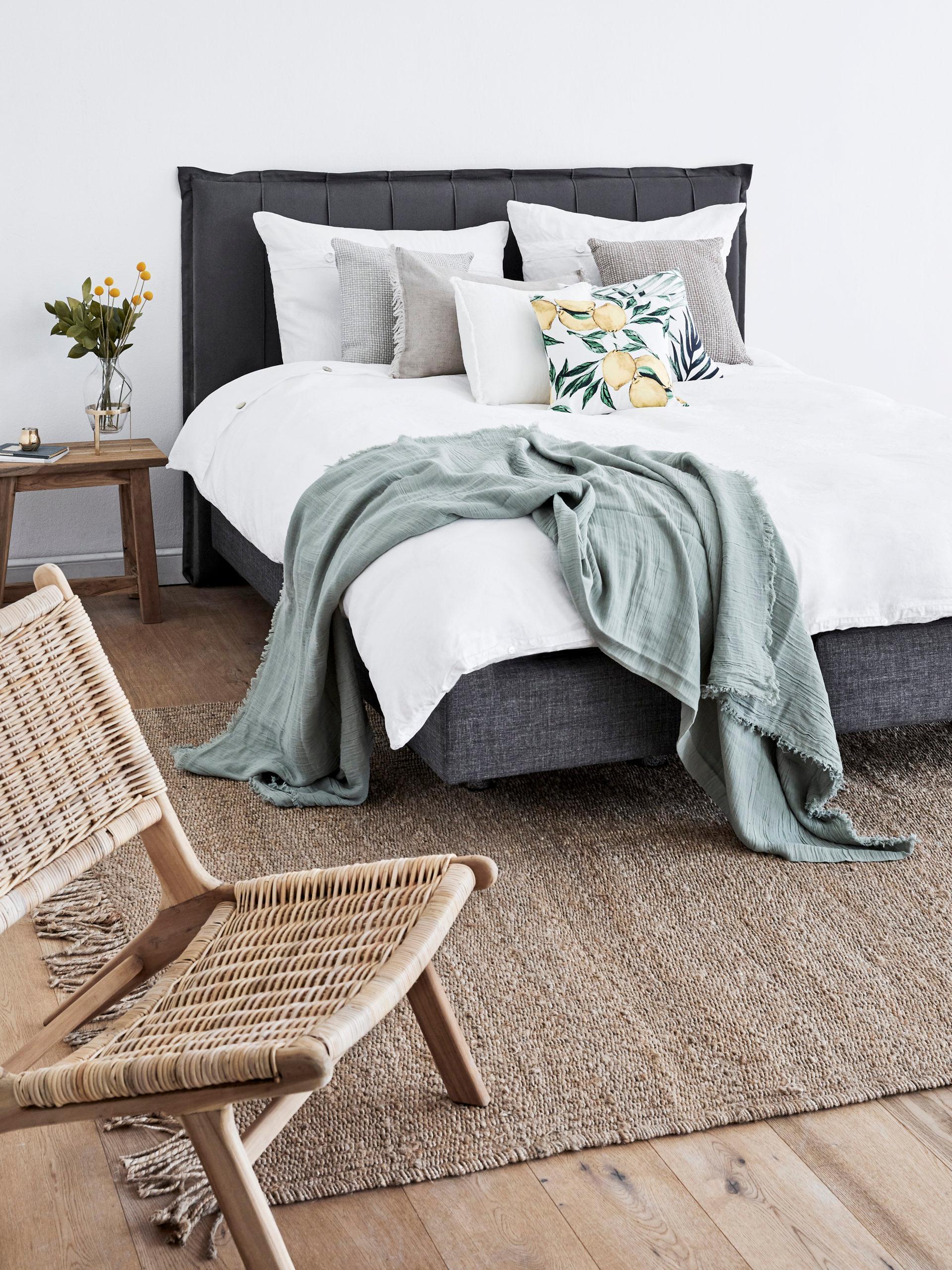 Sypialnia z dużym łóżkiem z białą pościelą i kocem w szałwiowej zieleni