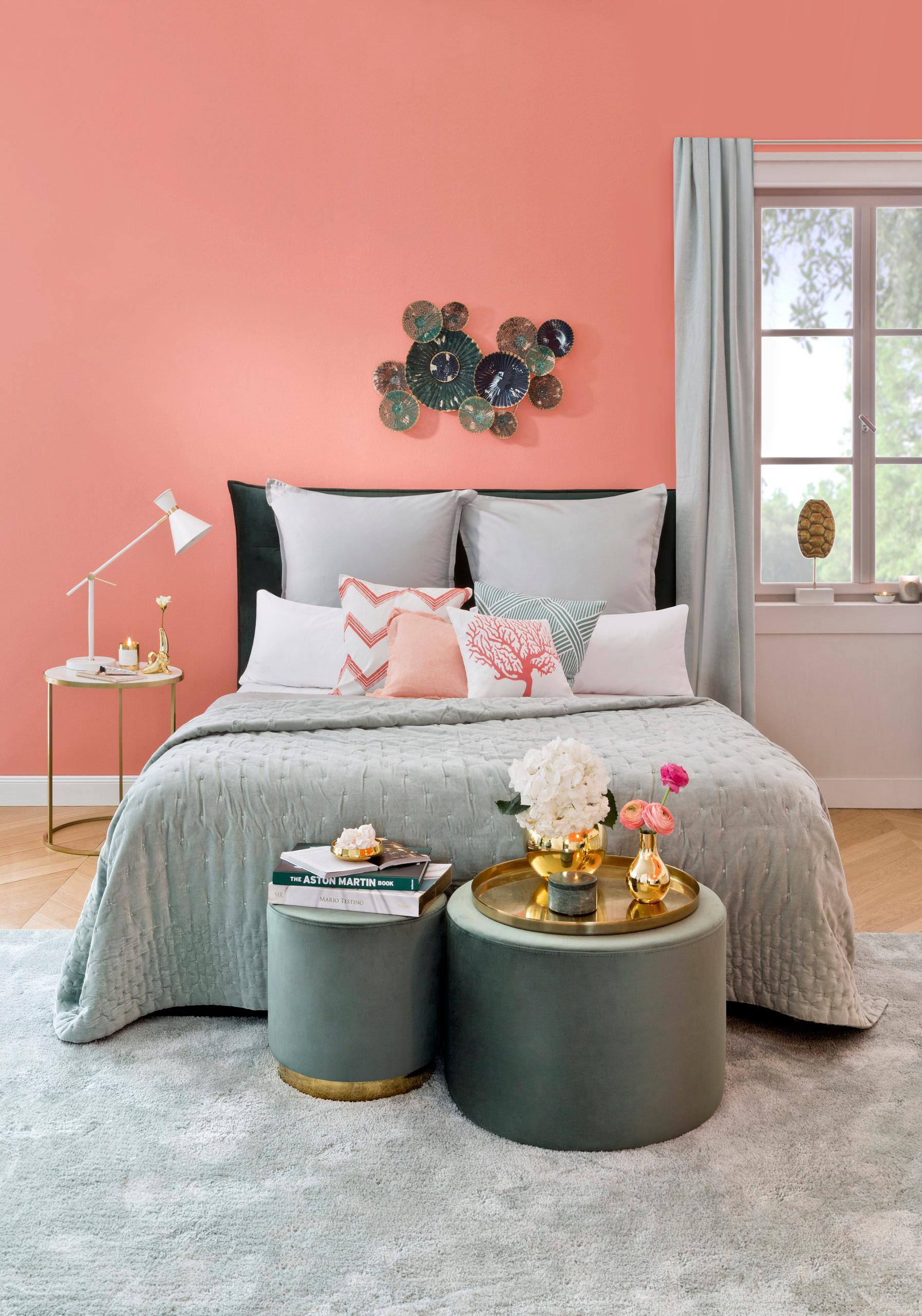 Sypialnia z brzoskwiniowymi ścianami i dodatkami takimi jak pufy i kapa w szałwiowej zieleni
