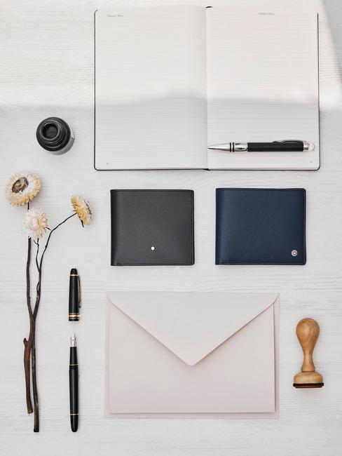 Otwarty notes, koterta, długopis oraz kwiaty leżące na biurku