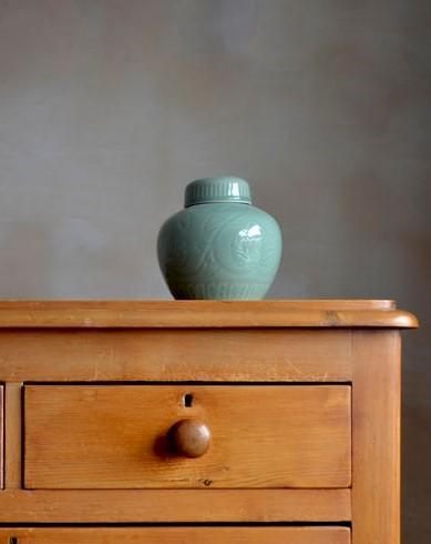 Fragment drewnianej komody, na której stoi niebieski wazon