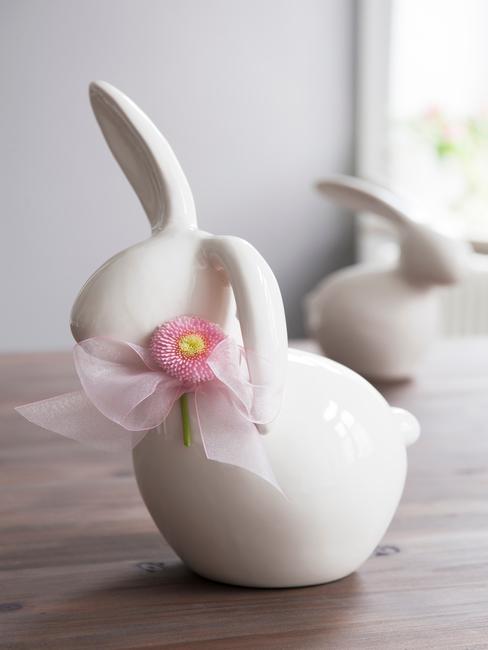 Biały, ceramiczny zajączek wielkanocny z kokardą na szyi i stokrotką